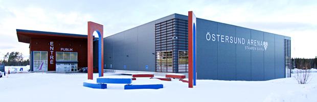 Vybild på Östersund Arena. Grå byggnad med röd entre allt i vinterskrud.